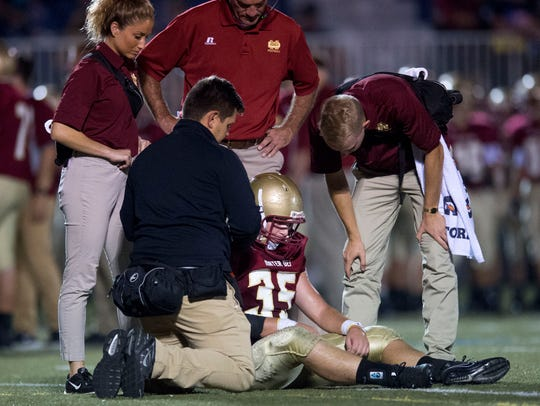 Mater Dei coaching and medical staff examine Iric Singer