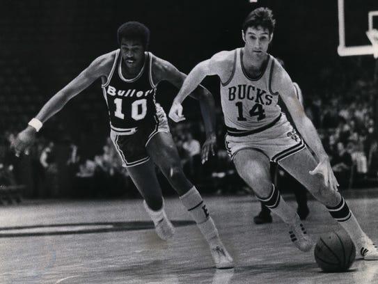Jon McGlocklin of the Milwaukee Bucks dribbles past