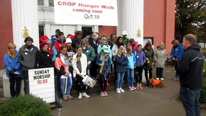 First Baptist Church pastor Rev. William Stoklosa, right, offers a prayer of encouragement last October as participants prepared for their annual CROP Hunger Walk through Hamilton to help end hunger. This year's event will be held Oct. 18, although since it is virtual participants can walk anywhere and anytime.