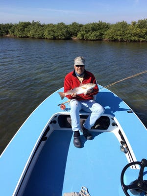 Hell's Bay Boat Works founder Hal Chittum, with a chilly fall redfish, hopes to revolutionize blue water boat building.