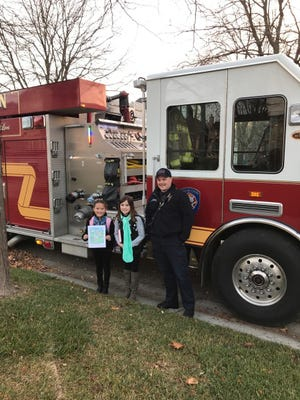 Madelyn Sabat (left) and Delaney Lovell with South Lyon Fire  Lt. Tim Wilson.