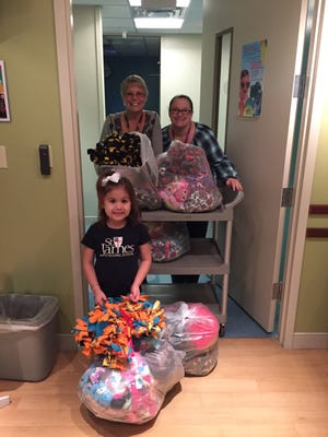Alondra Vela-Gamez (bottom left), a cancer survivor and Pre-K student at St. James Episcopal School, delivered tie blankets to cancer patients at Driscoll Children's Hospital.