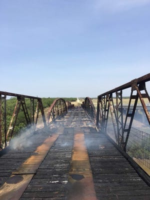 "The ""12-Mile Bridge"" in Runnels county where County Road 129 crosses the Colorado River smolders as volunteers from the Ballinger VFD extinguished the blaze that consumed it."