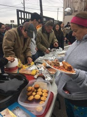 Volunteers hand out meals to the homeless at the Good