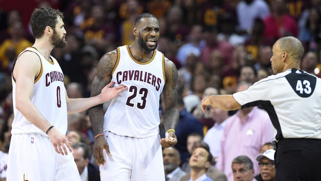Cleveland Cavaliers forward LeBron James (23) questions a call with referee Dan Crawford (43) in front of Cavaliers forward Kevin Love (0) during the third quarter in Game 4.