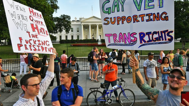 """Protesters gather in front of the White House on July 26, 2017, after President Trump announced that transgender people may not serve """"in any capacity"""" in the US military."""