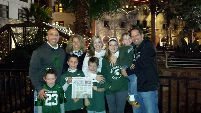 The Lutz and Toth families stopped for a photo with their hometown newspaper at the Gaylord Texan Hotel. This is the hotel in Arlington, Texas, where the Michigan State University football team stayed. Both families went to the Cotton Bowl. Brian Toth is the principal at Centennial Middle School in South Lyon. Their daughter, Taylor, attends Muir and son, Jake, attends Heritage. The Lutz family is also pictured. Heather is a teacher at Milford High, and Chip is a teacher at Muir. Kids, Carson and Ashlyn, both attend Heritage.