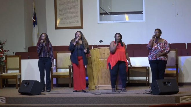The First Missionary Baptist Church Praise Team leads praise and worship during a service prerecorded on Saturday for broadcast via YouTube on Sunday morning.