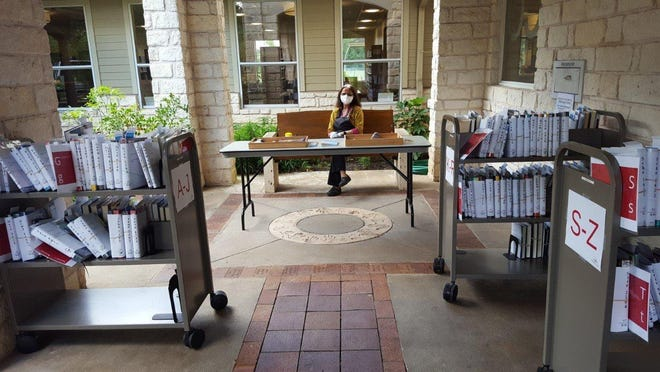 Manisha Mehta works the curbside pick up table at Westbank Library for patron picking up reserved materials June 3.