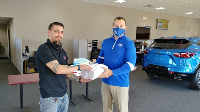 """Ionia High School Principal Ben Gurk (right) gives letters written by IHS students to WION's """"Popeye John"""" as part of the Treasures for Troops drive, which took place Nov. 2-6 in Ionia, Montcalm and Kent counties. The community donated items to various locations in the three counties that will be sent overseas to servicemen and women deployed overseas. This year marked the seventh annual drive. There were 224 boxes sent overseas as part of the drive, according to a press release."""
