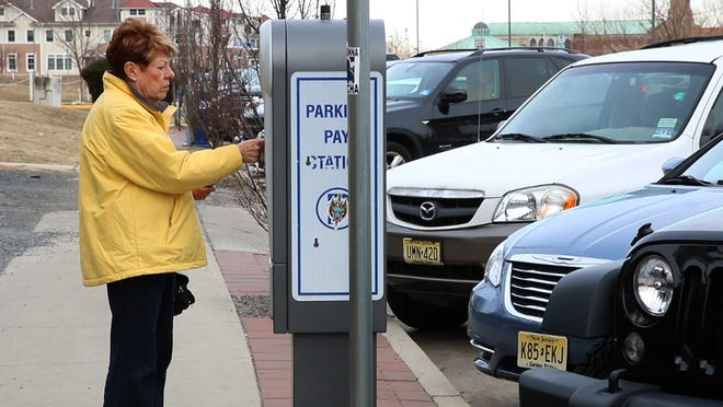 A woman pays for parking at a station on Lake Avenue in Asbury Park.