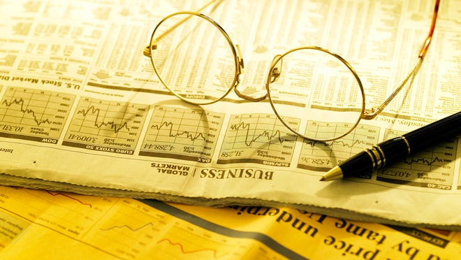 business article/a newspaper and a glasses pen