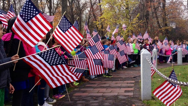Parsippany third grade students wave their flags at the Veterans Day ceremony at Veterans Memorial Park.