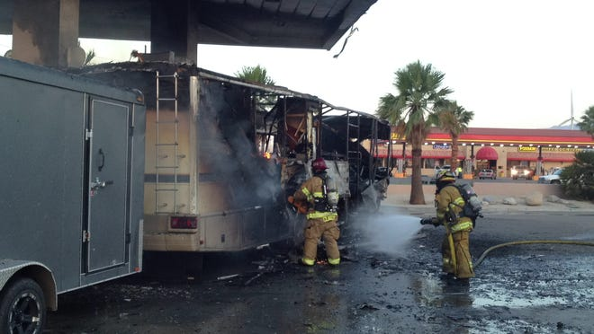 Palm Springs firefighters put out flames that destroyed a motor home at a Chevron gas station at Indian Canyon Drive and Garnet Avenue Thursday morning. A family of five was inside, but no one was injured.