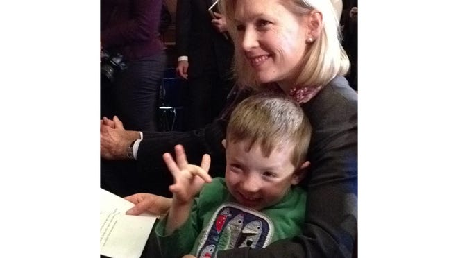 Sen. Kirsten Gillibrand with son Henry waiting to speak at a Jan. 7 news conference. Henry was waving to Sen. Charles Schumer.
