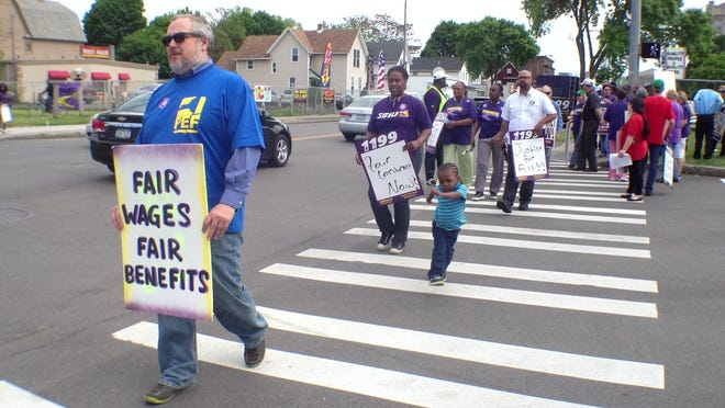 """Devery Reid-Holmes follows son Daniel Martin during a picket Friday afternoon by 1199 SEIU at Unity Health System's St. Mary's Campus. Reid-Holmes is part of 1199 SEIU at Strong Memorial Hospital and came to Unity to """"support my sisters and brothers in our fight."""""""