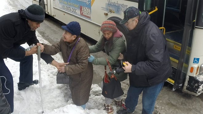 Commuters help each other get over mounds of snow and ice in White Plains after getting off the Westchester Bee-Line bus Monday.