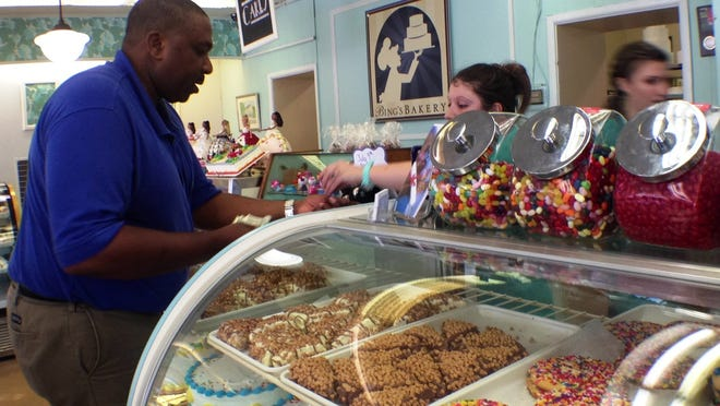 """Sylvester Johnson, the University of Delaware's Director of Facilities Custodial and University Services, pays for cookies Thursday morning at Bing's Bakery in Newark. The Main Street business is seeing a steady stream of customers since appearing Tuesday night on the TLC series """"Buddy's Bakery Rescue."""""""