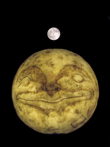 The Harvest Moon rises over the Man in the Moon sculpture