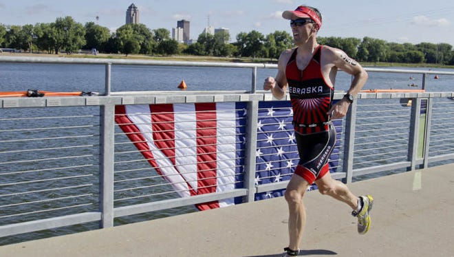 Gerald Kubiak of Omaha, Neb., crosses the bridge at Gray's Lake Park while competing in the 5150 U.S. Championship at the Hy-Vee Triathlon on Sunday, Sept. 1, 2013, in Des Moines, Iowa.