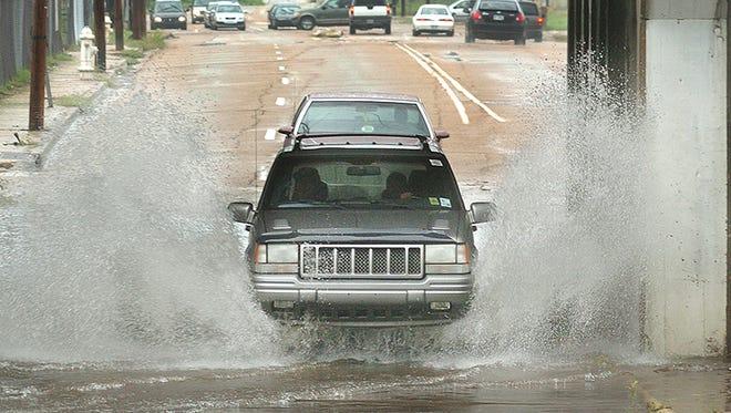 File photo of motorist plowing through flood water under the railroad bridge along Monument Street in Jackson.