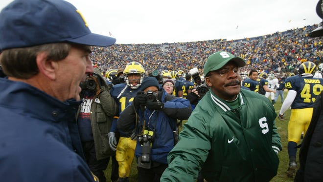 Michigan State coach Bobby Williams, right, just barely brushed hands with Michigan coach Lloyd Carr during at Michigan Stadium on Nov 2, 2002. U-M got an easy 49-3 win.