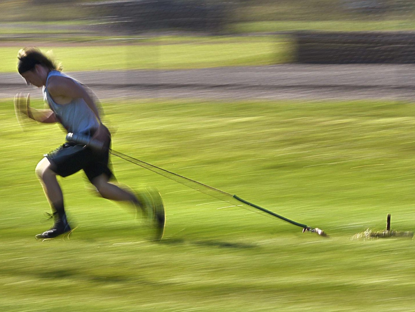 Milaca's Ted Blenkush pulls a weighted sled while doing sprints Tuesday during practice.