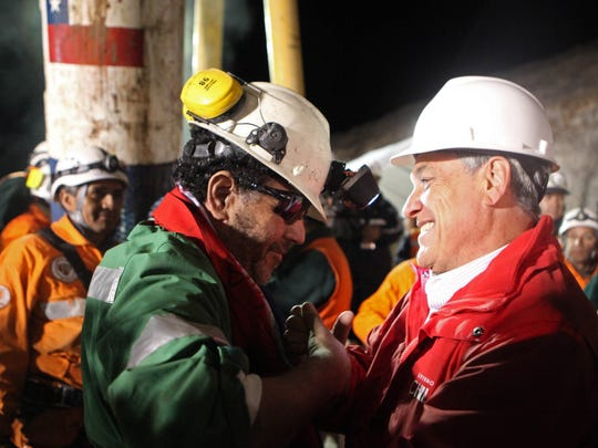 In this photo released by the Chilean government, the last miner to be rescued, Luis Urzua (left), shakes hands with Chile's President Sebastian Pinera after being freed from the collapsed San Jose gold and copper mine where he had been trapped with 32 other miners for over two months near Copiapo, Chile, on Oct. 13, 2010.