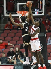 U of L's Lance Thomas (1), right, blocks a shot made by Bryant Bulldog Brandon Carroll during the second half of play against the visiting Bryant Bulldogs at the KFC Yum! Center on Monday night. Louisville won the game 102-59. Dec. 11, 2017