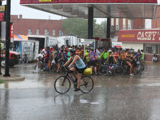 A RAGBRAI rider pedals through the rain as a mass of