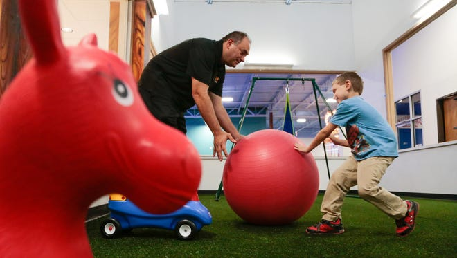 Brendan Schneider, 8, of Washington Township, pushes an over-sized ball over to his father, Tom Schneider of Washington Township while playing in a room before a ribbon cutting ceremony at Play-Place for Autistic Children in Sterling Heights on Friday September 9, 2016.