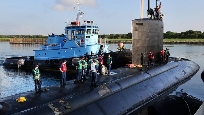 The crew of the Navy's newest nuclear-powered attack submarine, the USS Minnesota, get ready to dock at the Naval Ordinance Test Unit's wharf in Port Canaveral, Fla., before a tactical certification cruise in the Florida straits off the coast of Brevard County.