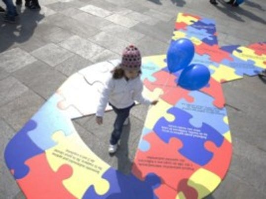 A child walks over the sign of Autism Awarness in Bucharest city April 2, 2014. International Autism Awareness Day was marked by a march downtown Bucharest and the blue lighting up of several important institutional buildings in Bucharest. AFP PHOTO / MIRCEA RESTEA