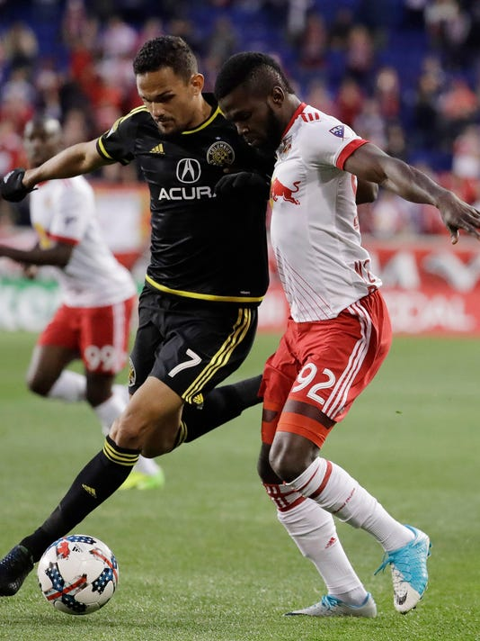 Columbus Crew midfielder Artur, left, and New York Red Bulls defender Kemar Lawrence compete for the ball during the first half of an MLS soccer match, Saturday, April 22, 2017, in Harrison, N.J. Artur left the game with an injury suffered during the play. (AP Photo/Julio Cortez)
