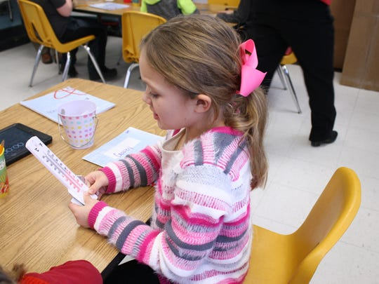 Gabriella Forbidusi, an 8-year-old second-grader at Palmer Elementary School, uses a thermometer during a Project Lead the Way lesson on Jan. 9.
