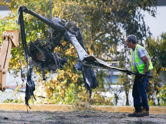 The wreckage of a crashed helicopter is removed from
