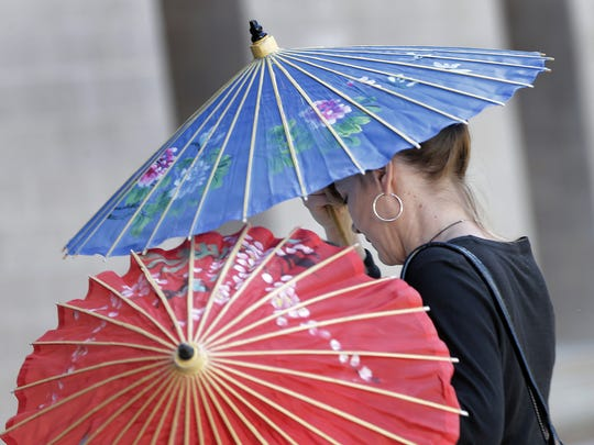 Former EPISD administrator Vanessa Foreman shields herself using umbrellas as she enters the U.S. Courthouse early Thursday morning. Foreman was a Priority Schools Division director assigned to Jefferson High School, and later Title I schools director for EPISD. She was fired in June 2013.