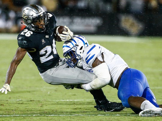 University of Memphis defender Genard Avery (right) tackles University of Central Florida receiver Otis Anderson (left) during fourth quarter action in Orlando, Fl., Saturday, September 30, 2017.