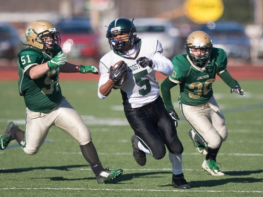 Woodstock's Ben Marsicovetere races away from Windsor defenders during the Division III high school football state championship game on Saturday at Rutland.