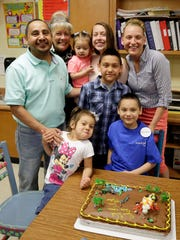 Mateo Meza, 9, seated in blue, poses with his family at his Grant Elementary School classroom Thursday, May 5, 2016, in Sheboygan. Meza, a third-grade student, had his wish for a Disney World trip granted through the Make-A-Wish Foundation. Meza had a heart transplant last July and a surprise party was held for the presentation.