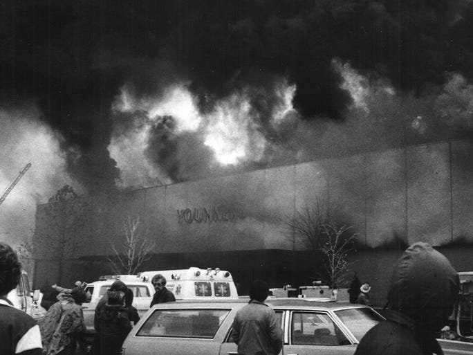 East side of store in flames, sending torrents of black smoke up.