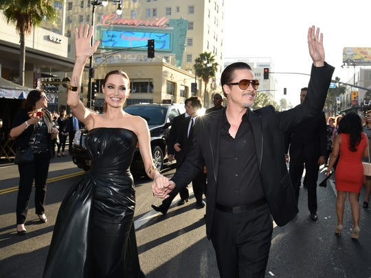 """Angelina Jolie and Brad Pitt arrive at the world premiere of """"Maleficent"""" at the El Capitan Theatre. A notorious red-carpet prankster was arrested on suspicion of battery of Pitt, who was unharmed."""