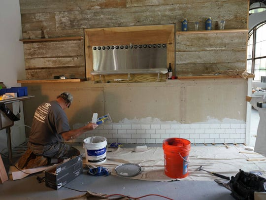 Tiles are placed at the tasting room's bar at Wilmington Brew Works on Miller Road, located at the long-dormant former site of the Harper-Thiel Electroplating Co.