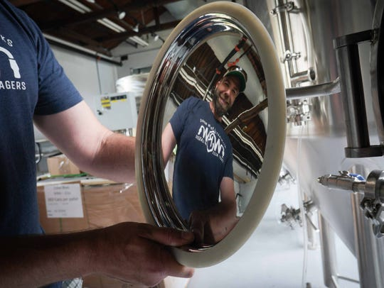Craig Wensell, chief executive officer and head brewer at Wilmington Brew Works, reflects in a door of a beer tank at his brewery that he plans on opening by the end of June.