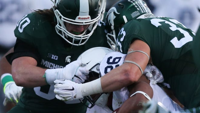 Michigan State's Riley Bullough and Jon Reschke tackle Penn State's Saquon Barkley during the first half Saturday in East Lansing.