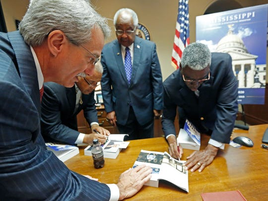 "Howard Catchings, of Catchings Insurance Agency, second from right, watches as Gerard Gibert of Venture Technologies, left, and Bishop Ronnie Crudup Sr., of the Fellowship of International Churches, second from left, and Dolphus Weary, of the Rural Education and Leadership Christian Foundation, right, autograph each other's copies of the 2017 bicentennial version of the Official and Statistical Register of the State of Mississippi, also called the ""Blue Book,"" released Tuesday at the Capitol in Jackson. The introductory section of the publication includes a brief history of the state as well as touts some of the state's sports legends, business leaders and artists, authors and musicians. All the attendees are included in the newest version."
