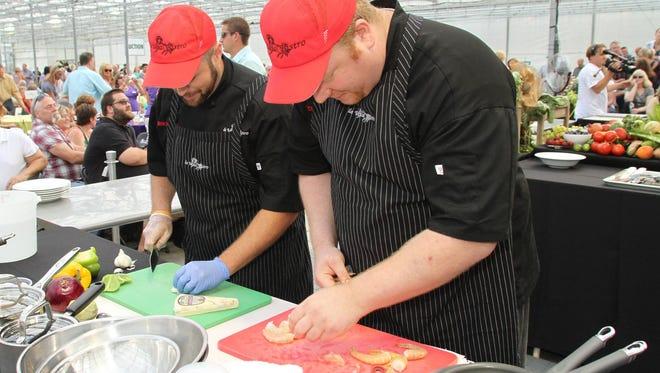 La Vita Bistro Executive Chef Eirik Kauserud, right, prepares large shrimp to accompany his dish which must include the secret ingredient, kohlrabi.