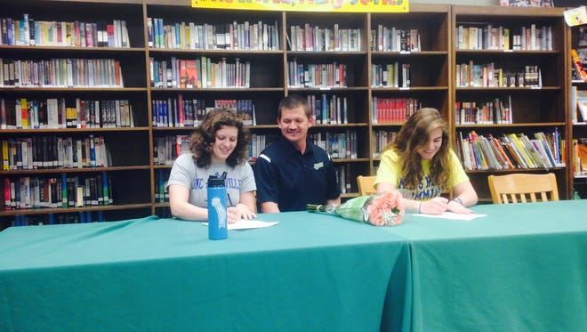 Reynolds seniors Anna Catherine Nazemi (UNC Asheville) and Brin Sampson (Mars Hill) signed with college swim teams on Friday alongside their coach, Eric Vess.