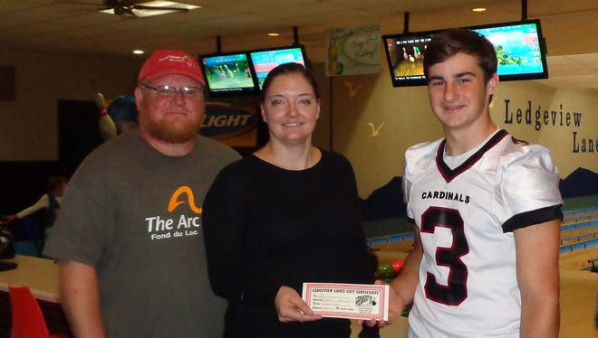 Fond du Lac High School (FHS) Senior Carver Nolan, public relations leader for the 2015-16 Cardinal's Nest, presents a $300 check to Harper Mruk, Director of Development, and Brian Shaver, Special Olympics Coordinator from The ARC of Fond du Lac at Ledgeview Lanes.  The donation is being shared by The ARC Fond du Lac and the special needs program at FHS to support recreational bowling activities for its members and students.
