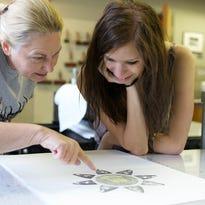 Print artist Rhea Edge works with student Nikki Schwontkowski during a previous Monoprint event.